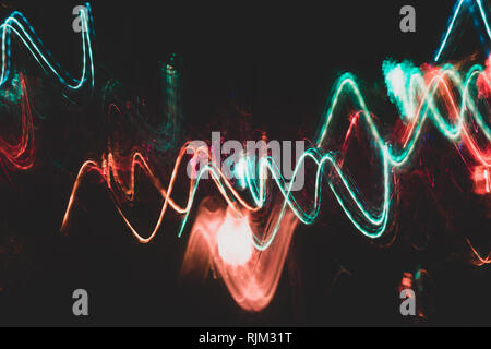 Colorful red and turquoise glowing wavy lines on black backdrop.  - Stock Photo