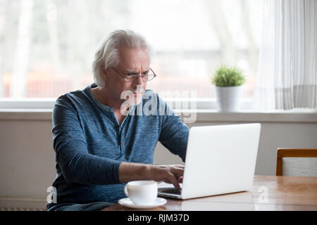 Serious mature man working on computer at home - Stock Photo