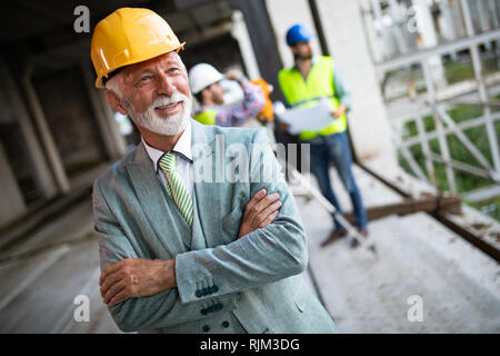 Confident construction engineer, architect, businessman in hardhat on building site - Stock Photo