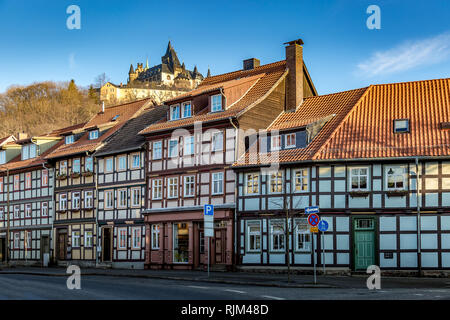 Half-timbered facades in the Harz with Wernigerode castle in the background - Stock Photo