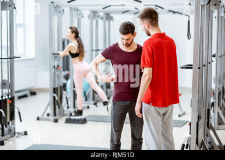 Therapist talking with man patient having problems with his back standing at the rehabilitation gym - Stock Photo