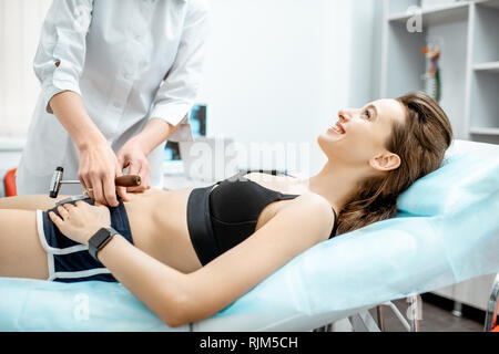 Young woman during the medical examination with neurologist testing reflexes in the office - Stock Photo