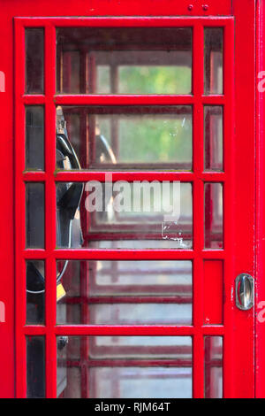 Detail of double red vintage english phone box, many small glass windows at door, interior view inside through it (copy space) - Stock Photo