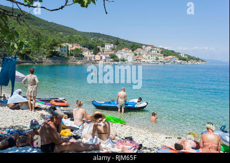Tourists on the beach in Valun, Cres, Croatia - Stock Photo