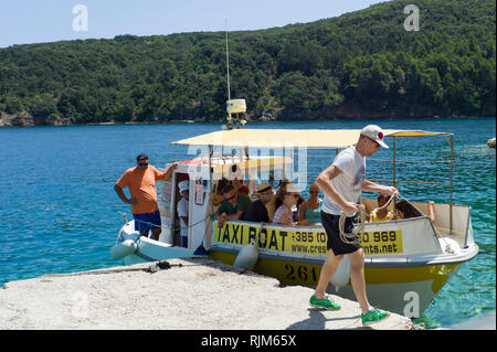 A small taxi boat ( ferry ) lands in the harbour of Valun village on the island of Cres Croatia - Stock Photo