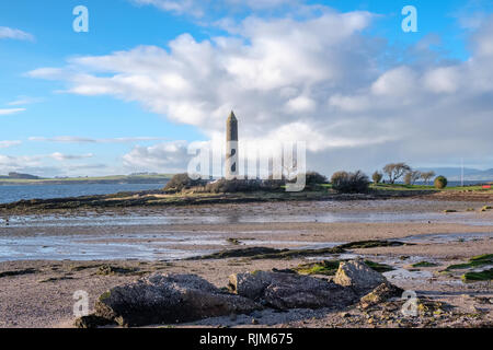 Largs foreshore looking past the Pencil Monument there to commemorate the Viking Battle of Largs in 1263. The Largs to Millport Ferry can be seen in t - Stock Photo