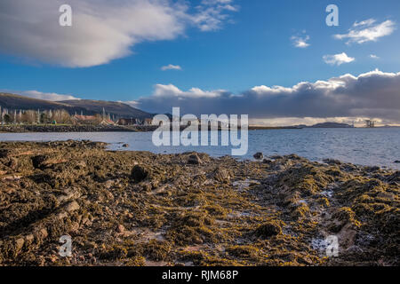 Largs Foreshore looking into the marina across a small bay and lichen covered rocks at low tide. With Hunterston in the far distance. - Stock Photo