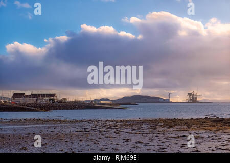 Largs Foreshore looking into the marina across a small bay at low tide with the cranes and wind turbine of Hunterston in the far hazy distance. - Stock Photo