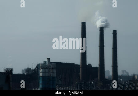 Smoke stack in working plant emitting smog and air pollution - Stock Photo
