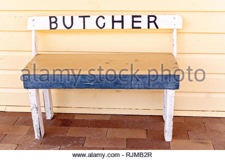 Vintage stool with butcher sign on pavement outside of shop front - Stock Photo