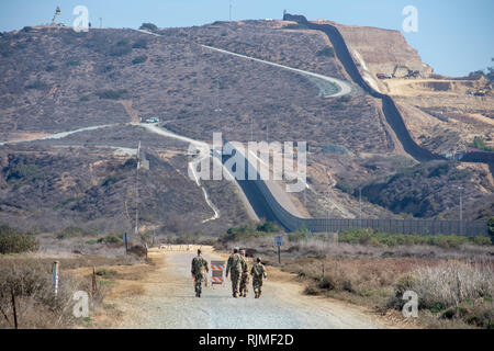 US Armed Forces soldiers in green military camouflage walk near double-layered secured international border wall between the United States and Mexico - Stock Photo