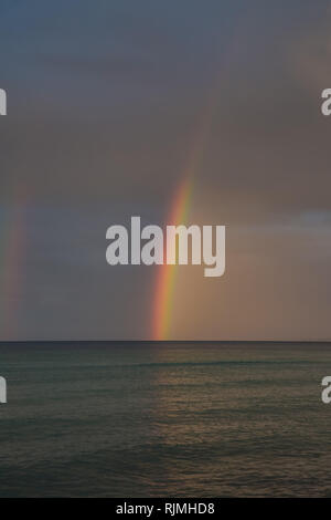Rainbow on the cloudy sky at the sea - Stock Photo
