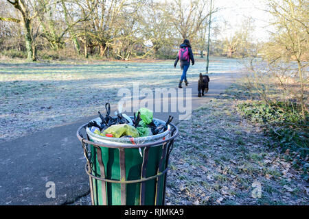 An overflowing dog waste bin on Barnes Common, London, SW13, UK - Stock Photo