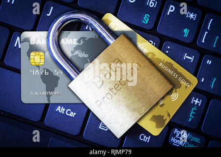Golden padlock on top of credit or debit cards on computer keyboard. Concept of Internet security, data privacy, cybercrime prevention for online shop - Stock Photo