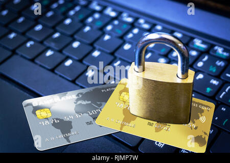 Golden padlock on top of fictitious credit cards on computer keyboard. Concept of Internet security, data privacy, cybercrime prevention for online sh - Stock Photo