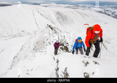 Climbers / mountaineers on a winter traverse of Sharp Edge, a ridge on Blencathra mountain in the Lake District National Park, Cumbria,UK - Stock Photo