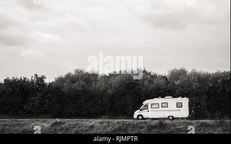 Fast RV camer van driving on the green dunes in Netheralnds during Euroeapn holidays - black and white - Stock Photo