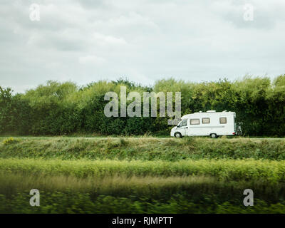 Fast RV camer van driving on the green dunes in Netheralnds during Euroeapn holidays - drive to the left