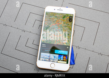 PARIS, FRANCE - SEP 26, 2016: Male hand holding New Apple iPhone 7 8 Plus smartphone after unboxing and testing by installing the app application software Apple Maps GPS flyover Paris France - Stock Photo