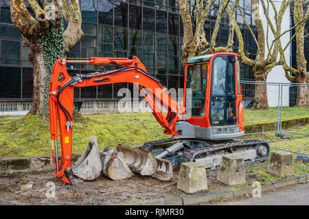 Small machine res excavator on sidewalk during repair works on street in urban environment - Stock Photo