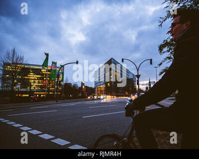 HAMBURG, GERMANY - MAR 21, 2018: man on bicycle standing on roadside waiting for green light in dusk time in front of Der Spiegel newspaper headquarter - Stock Photo