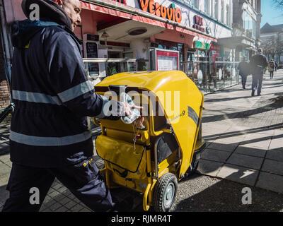 HAMBURG, GERMANY - MAR 20, 2018: Man in uniform pushing Deutsche Bank DHL German post yellow carriage with mail walking down street - Stock Photo
