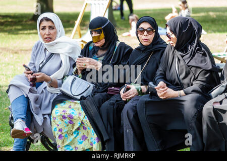 United Kingdom Great Britain England London Hyde Park public park Serpentine Road bench Middle Eastern Arab Muslim woman burqa Battoulah hijab sitting - Stock Photo