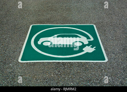 EV - electric vehicle charging station sign. 'E' sign on asphalt texture - Stock Photo