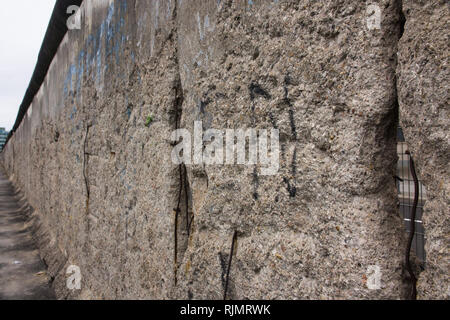 Berlin Wall original weathered section damaged with exposed iron bars and rough cement concrete texture in diagonal perspective filling the frame. - Stock Photo