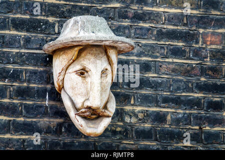 United Kingdom Great Britain England London Westminster Saint St. James's Church Piccadilly exterior garden wall stone sculpture carving face - Stock Photo