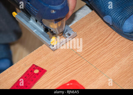 Electrical machine cutting a wooden plank - Stock Photo
