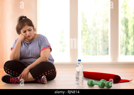 Depressed overweight woman sitting on the floor and doesn't wont to exercise - Stock Photo