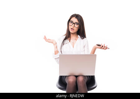 Shocked businesswoman. Surprised young woman in shirt with laptop and phone looking at camera and keep her mouth open while standing on white - Stock Photo