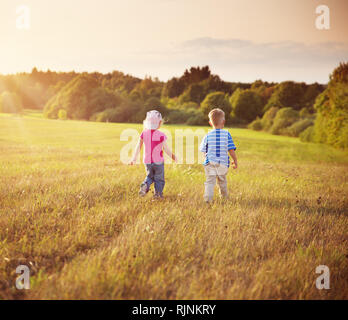 Boy and girl walking on the field in summer - Stock Photo