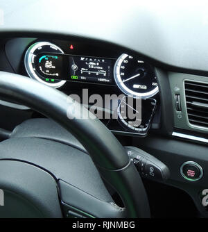 Speedometer arrow in reflection on the glass display of smartphone on the car dashboard under steering wheel - Stock Photo