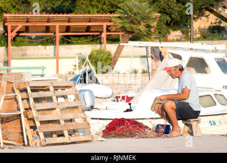 Prvic island, Croatia - August 23, 2018: Fisherman repairing his fishing net on pier with boats in the background - Stock Photo