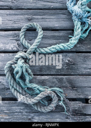 Blue rope on top of weathered wooden planks, full frame, close up - Stock Photo
