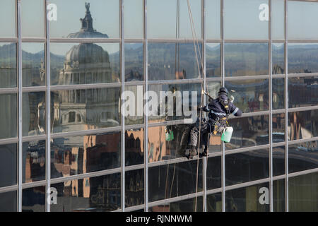 Abseiling Window Cleaner at Work with Nottingham Council House Reflecting in the Windows - Stock Photo