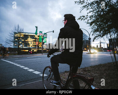 HAMBURG, GERMANY - MAR 21, 2018: Anonymous man on bicycle standing on roadside waiting for green light in dusk time - Stock Photo