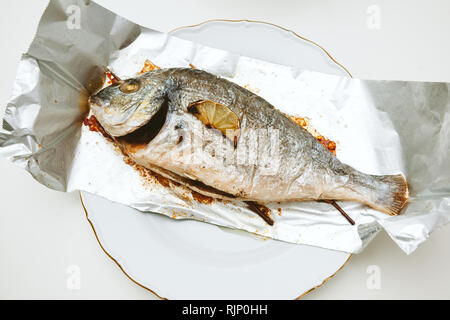 One gilt-head bream fish on the aluminum foil on white table - view from above od delicious food homemade - Stock Photo