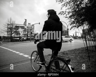 HAMBURG, GERMANY - MAR 21, 2018: Cinematic black and white of man on bicycle standing on roadside waiting for green light in dusk time - Stock Photo