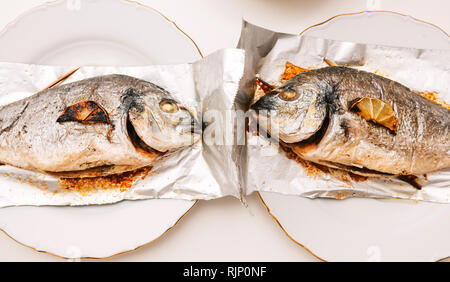Two gilt-head bream fish on the aluminum foil on white table - view from above od delicious food homemade filter instagram style - Stock Photo