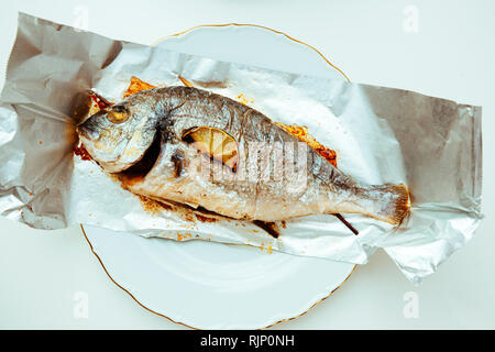 Two gilt-head bream fish on the aluminum foil on white table - view from above od delicious food homemade - Stock Photo