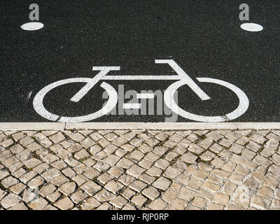 From above shot of white marking of bicycle sign on asphalt pavement on street - Stock Photo