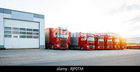 View of squadron group of new red cargo trucks parked in a row near warehouse building in bright sunset light - Stock Photo
