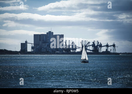 Small idyllic single sailing boat with white sail in blue water of sea on background of industrial manufacture on shore - Stock Photo