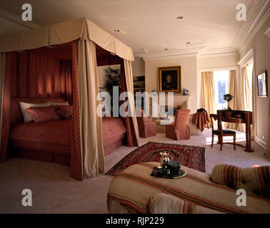 Cream drapes on bed in opulent bedroom - Stock Photo