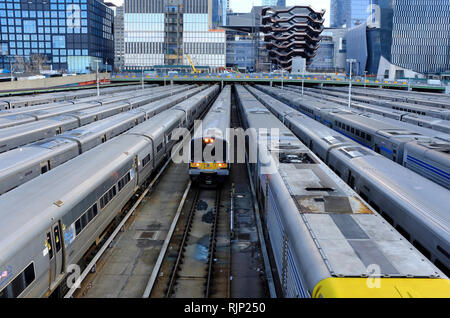 Trains in Long Island Rail Road's West Side Yard with 'Vessel' and Hudson Yards,a real estate development under construction in the background.NYC USA - Stock Photo