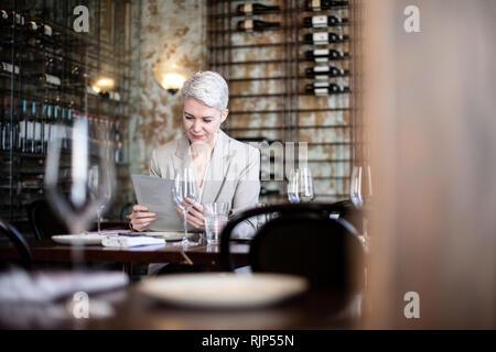 Businesswoman reading menu in a restaurant - Stock Photo