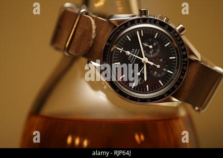 Omega Speedmaster watch on leather nato strap wrapped around bottle of single malt scotch on brown background - Stock Photo